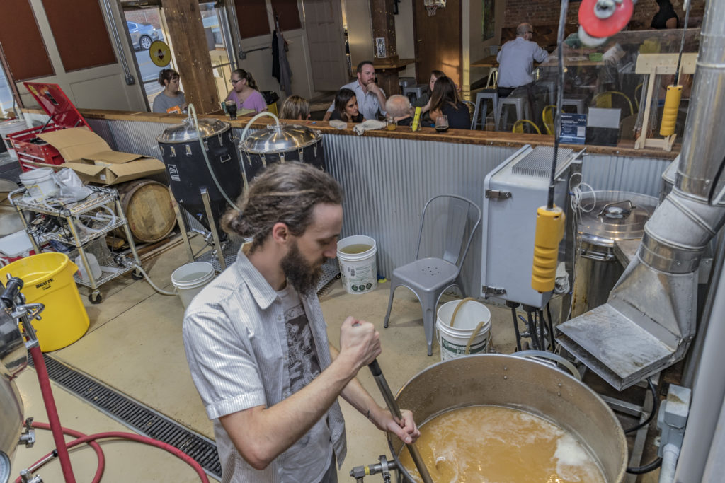 Man stirs craft beer in pot