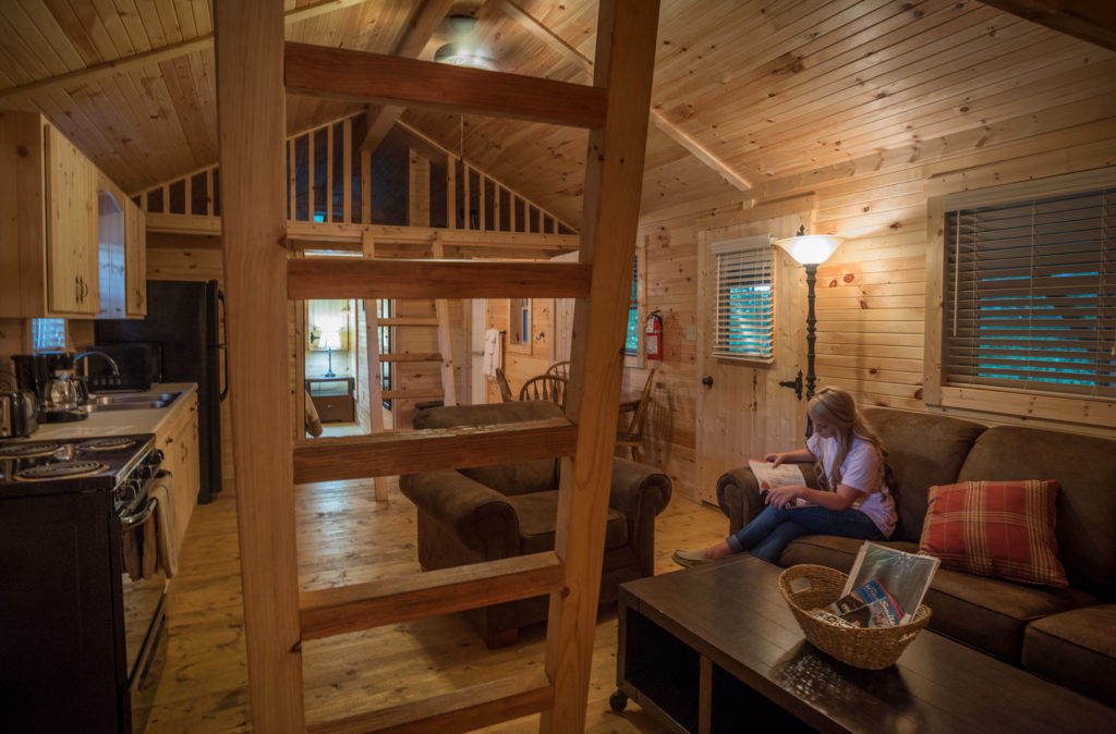 Woman reading on couch inside cabin