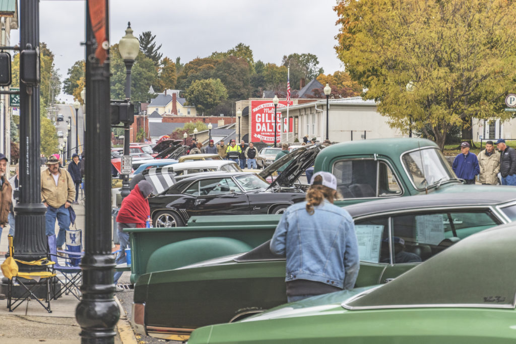 People look at classic cars and trucks on street
