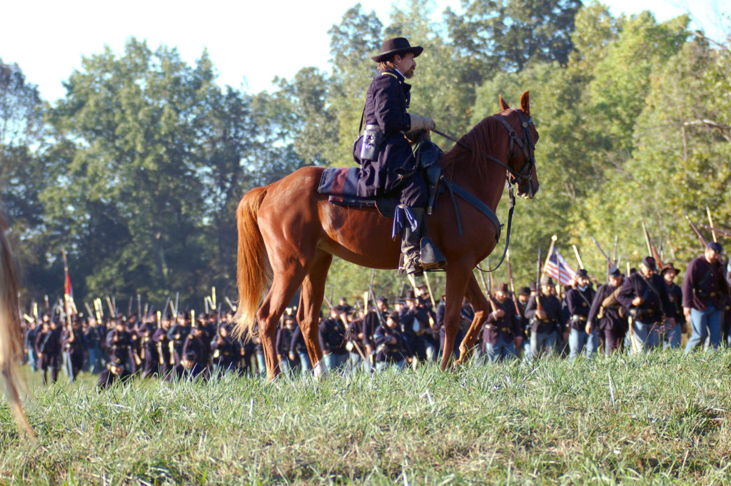 Union soldier sits atop horse in field during Civil War reenactment