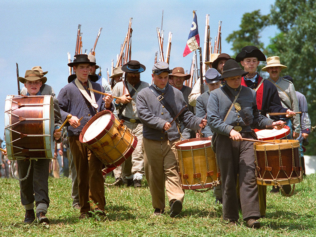Confederate soldiers march and play drums during a reenactment.